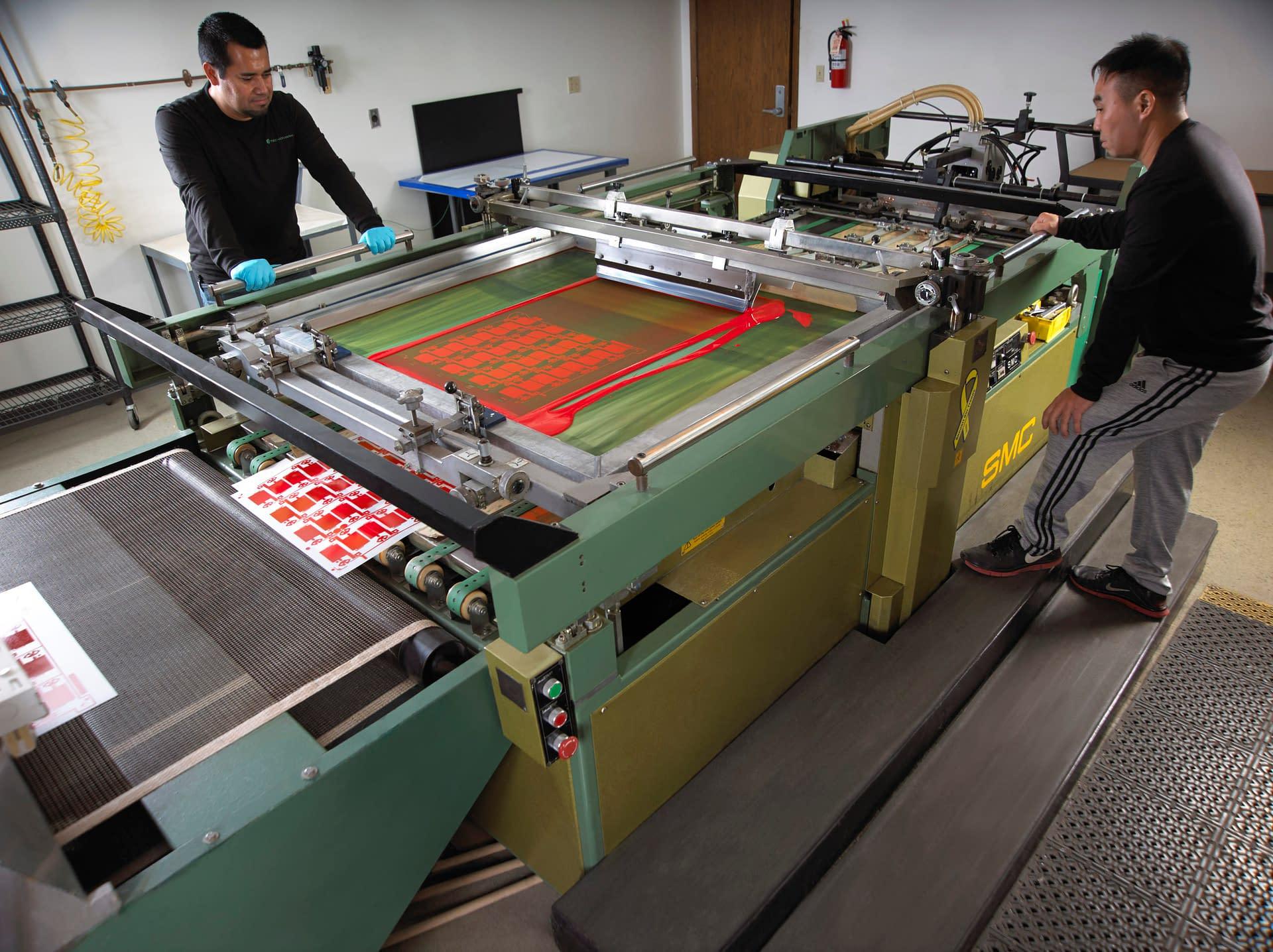 Technicians operating high speed silkscreen machine printing component overlays