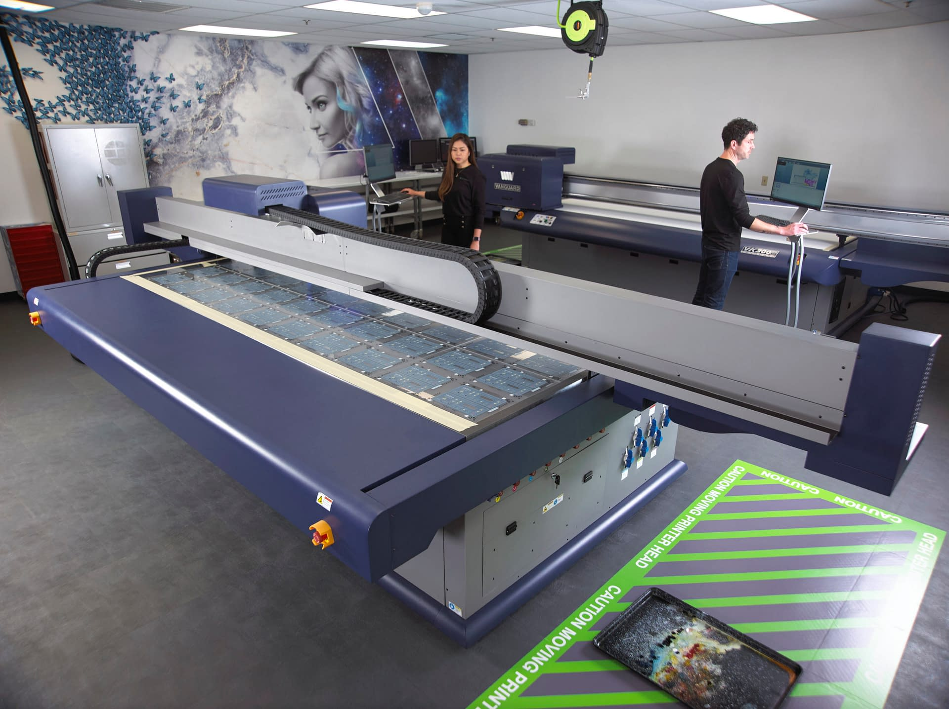 Technicians operating large format overlay printer