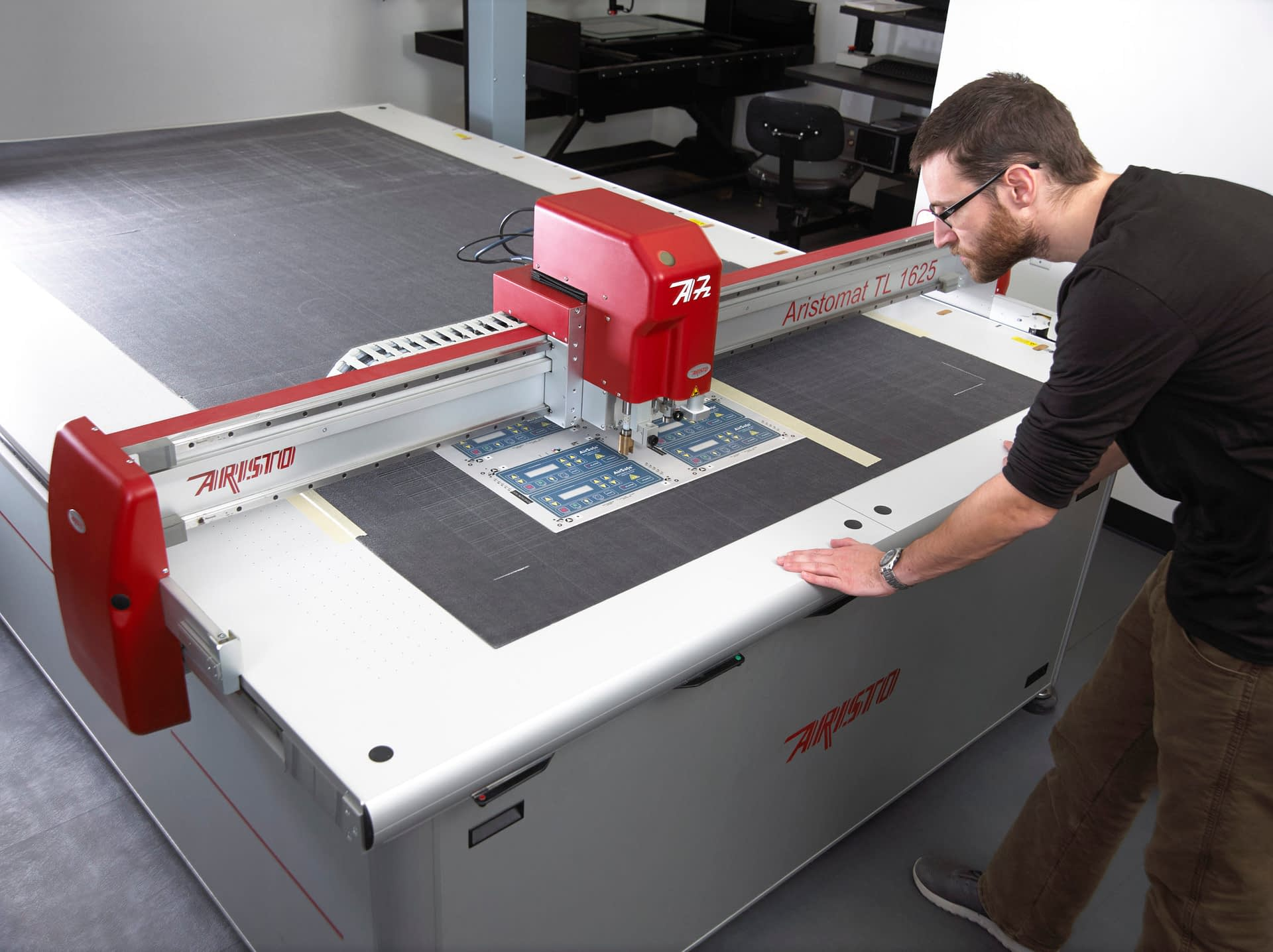 Technician using automated flatbed die cutter