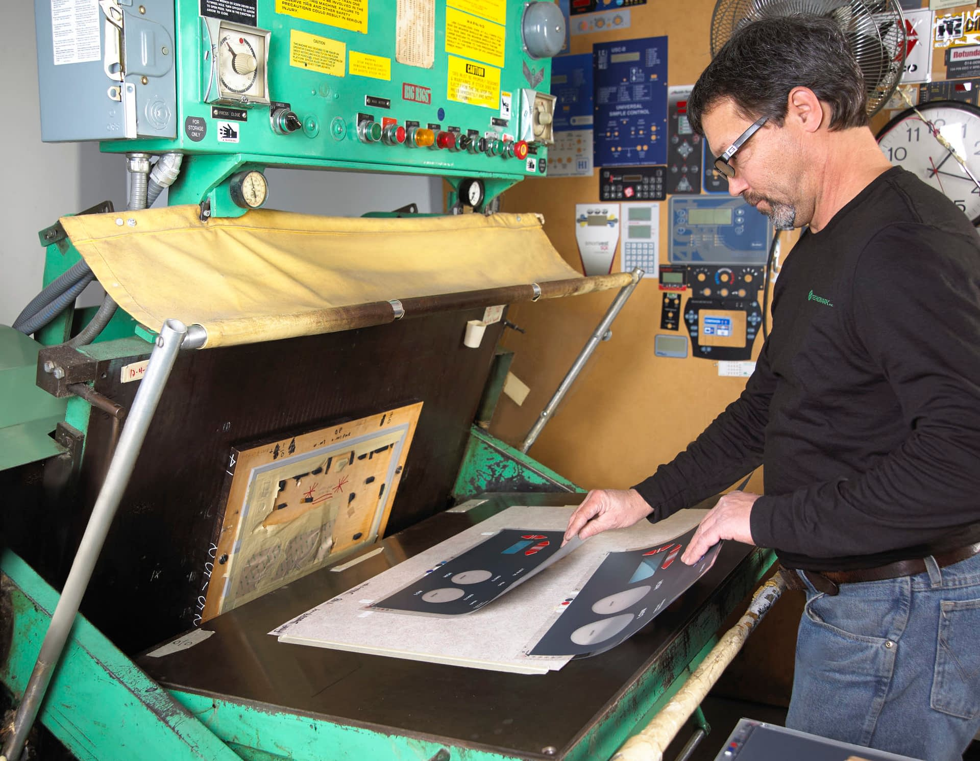 Technician using die cutter to cut a graphic overlay